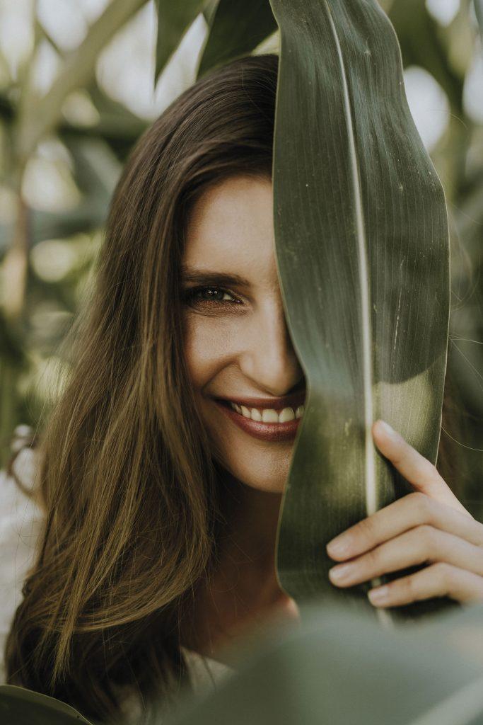 uśmiechnięta kobieta wyglądająca zza liścia. Liść zasłania jej pół twarzy