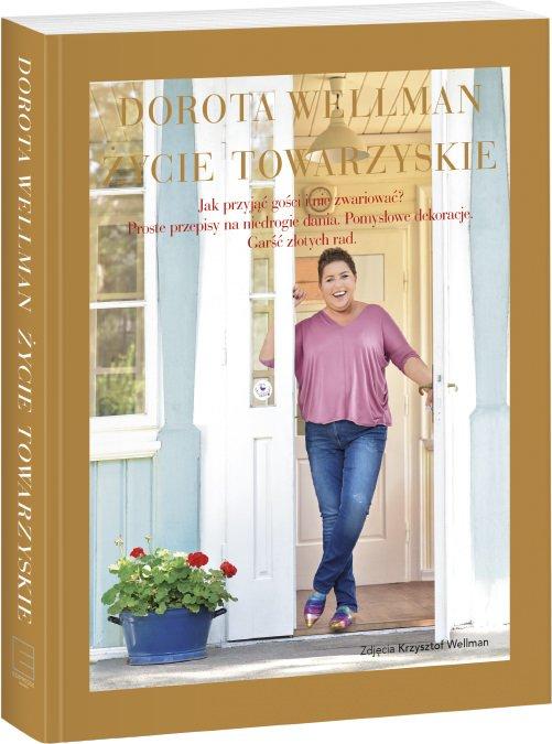 zdjęcie okładki, na której Dorota Wellman stoi w wejściu do swojego domu, ma super kolorowe buty i gustowna bluzką w kolorze różowym