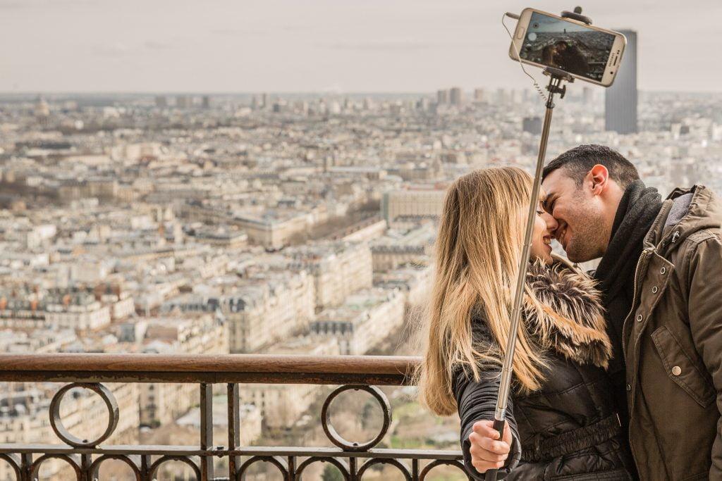 para całująca sie na dachu, dziewczyna trzyma aparat na selfie sticku