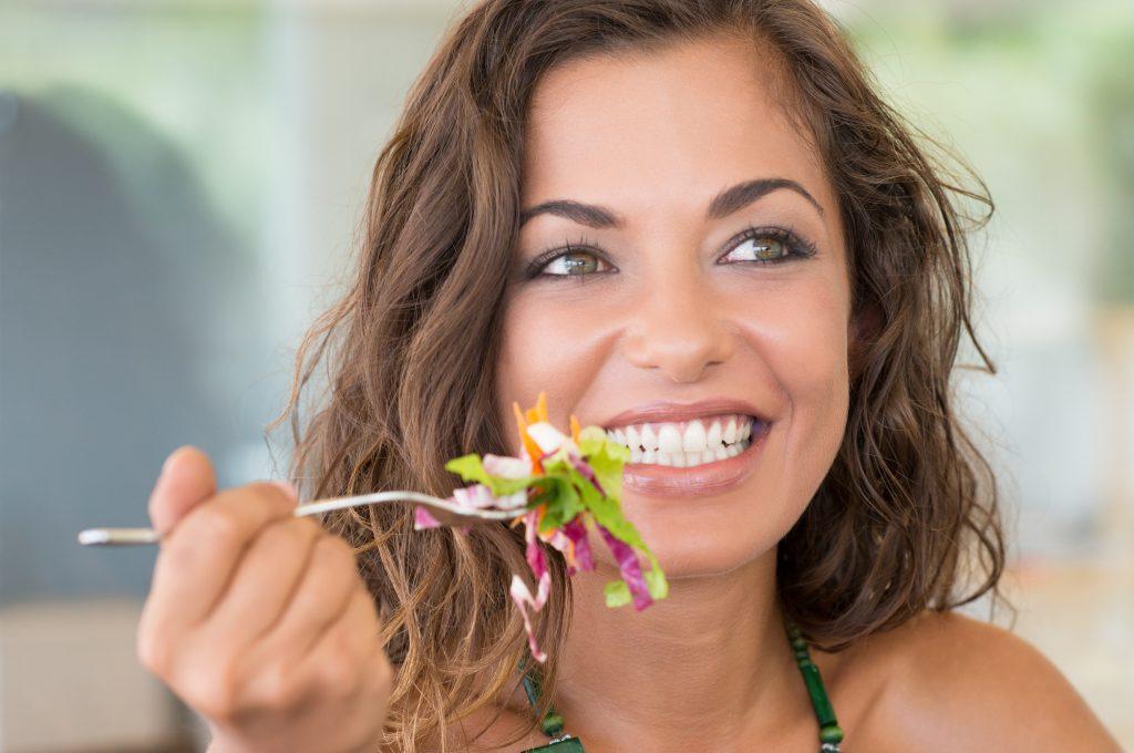 roześmiana dziewczyna je sałtkę, ma piękne białe zęby
