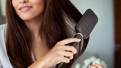 kobieta prostująca sobie ciemne włosy, prostownicą, fot.philips